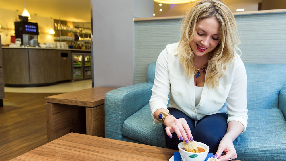 Show item 5 of 5. woman enjoying bread and soup at the airport lounge