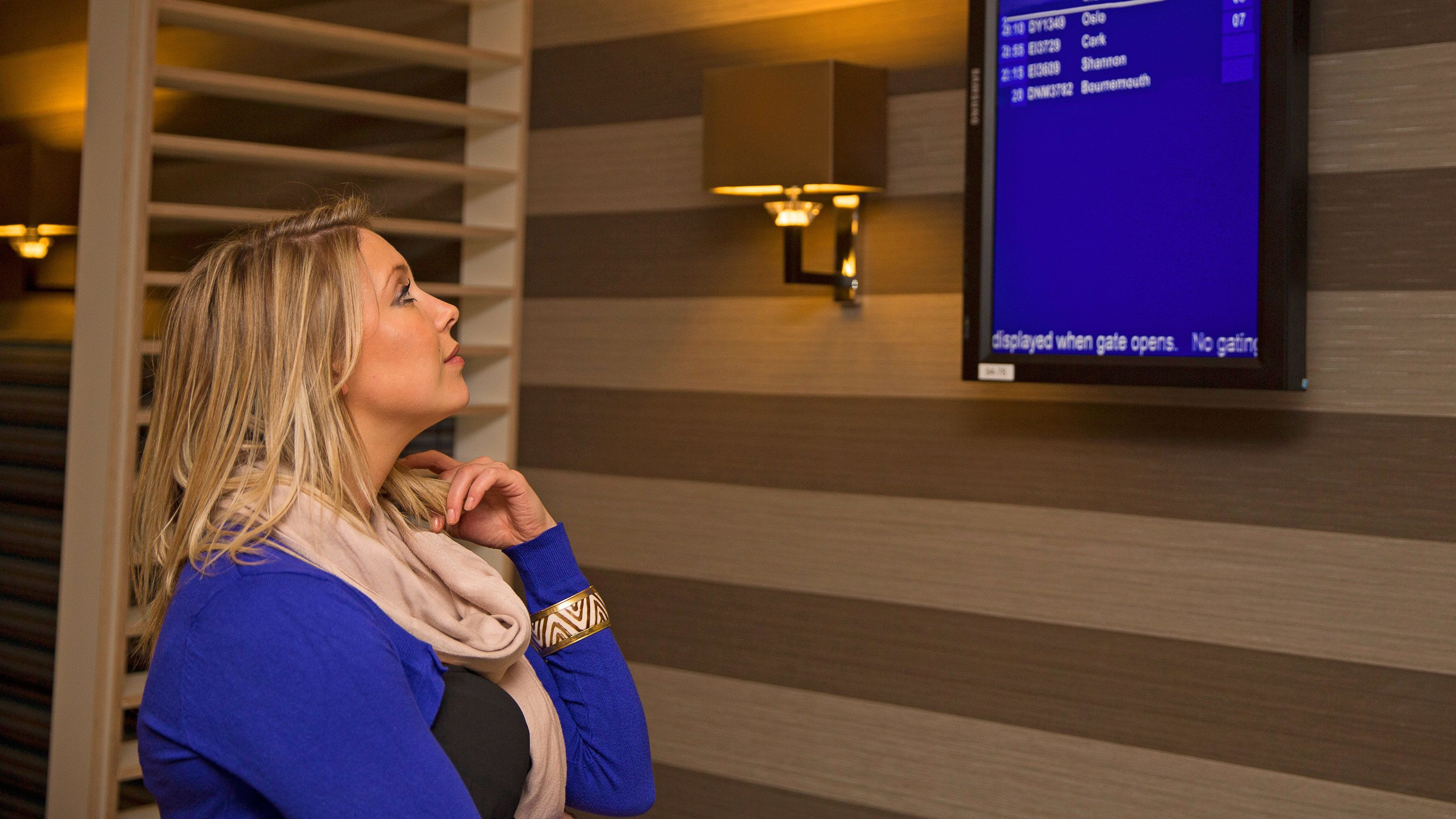Woman looking at flight information on an airport lounge monitor