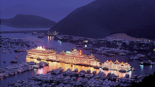 Boat lit up at night in the harbor in Hong Kong
