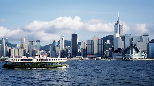 Boat on the water with city in the background in Hong Kong