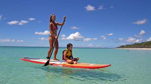 Woman and child on a stand-up paddle in Australia