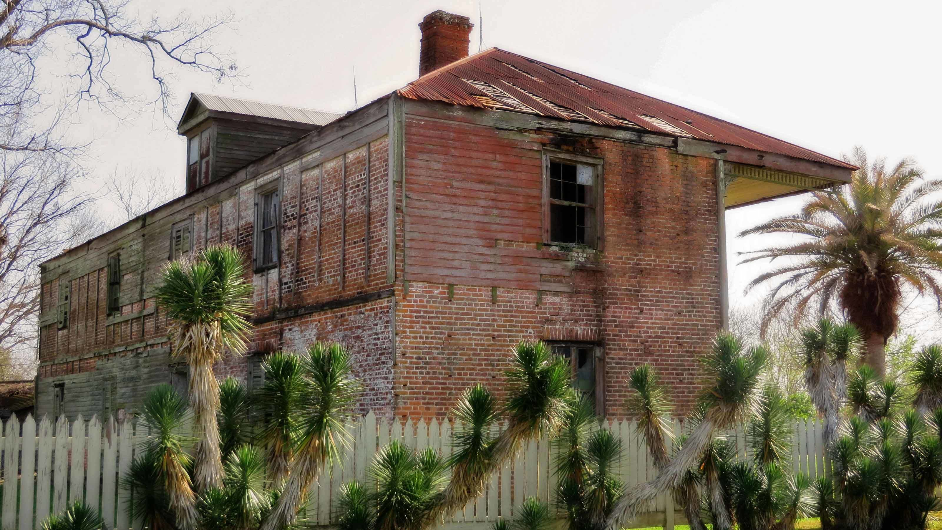 side view of old brick house with trees surrounding it