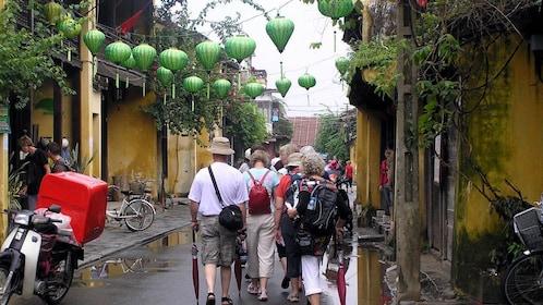 people walking along street with green lanterns