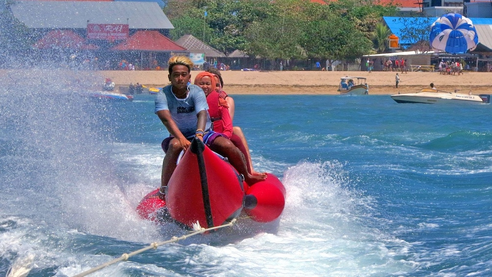 Show item 4 of 5. group on inflatable raft pulled by speedboat in Bali
