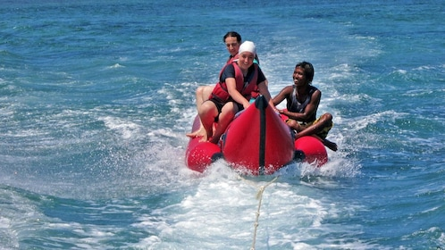 group hanging onto an inflatable raft pulled by a boat in Bali