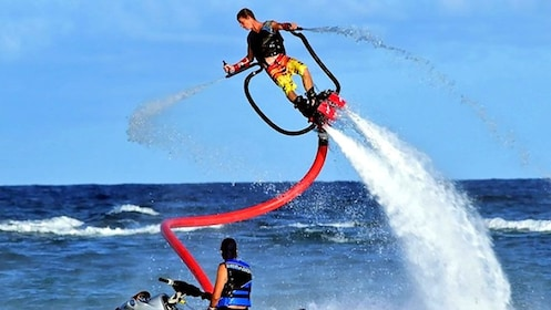 flyboarding man twisting in the air above water in Bali