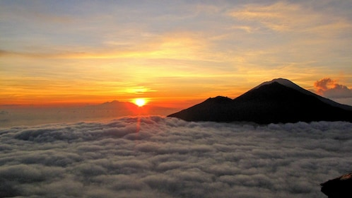 un rising above the clouds in Indonesia
