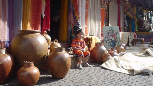 Young boy at a craft store selling colorful textiles and large pots in Sao Paulo