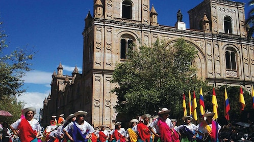 Costumed dancers performing in front of a gothic-style cathedral in Cuenca