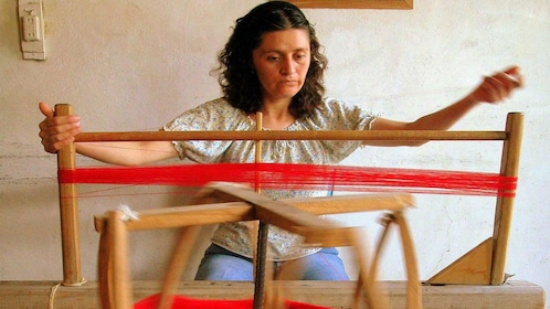 Woman weaving threat with a loom in Cuenca