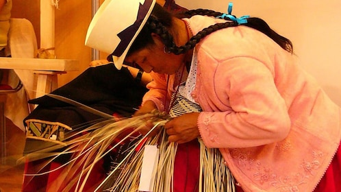 Local craftswoman weaving grass strands in Cuenca