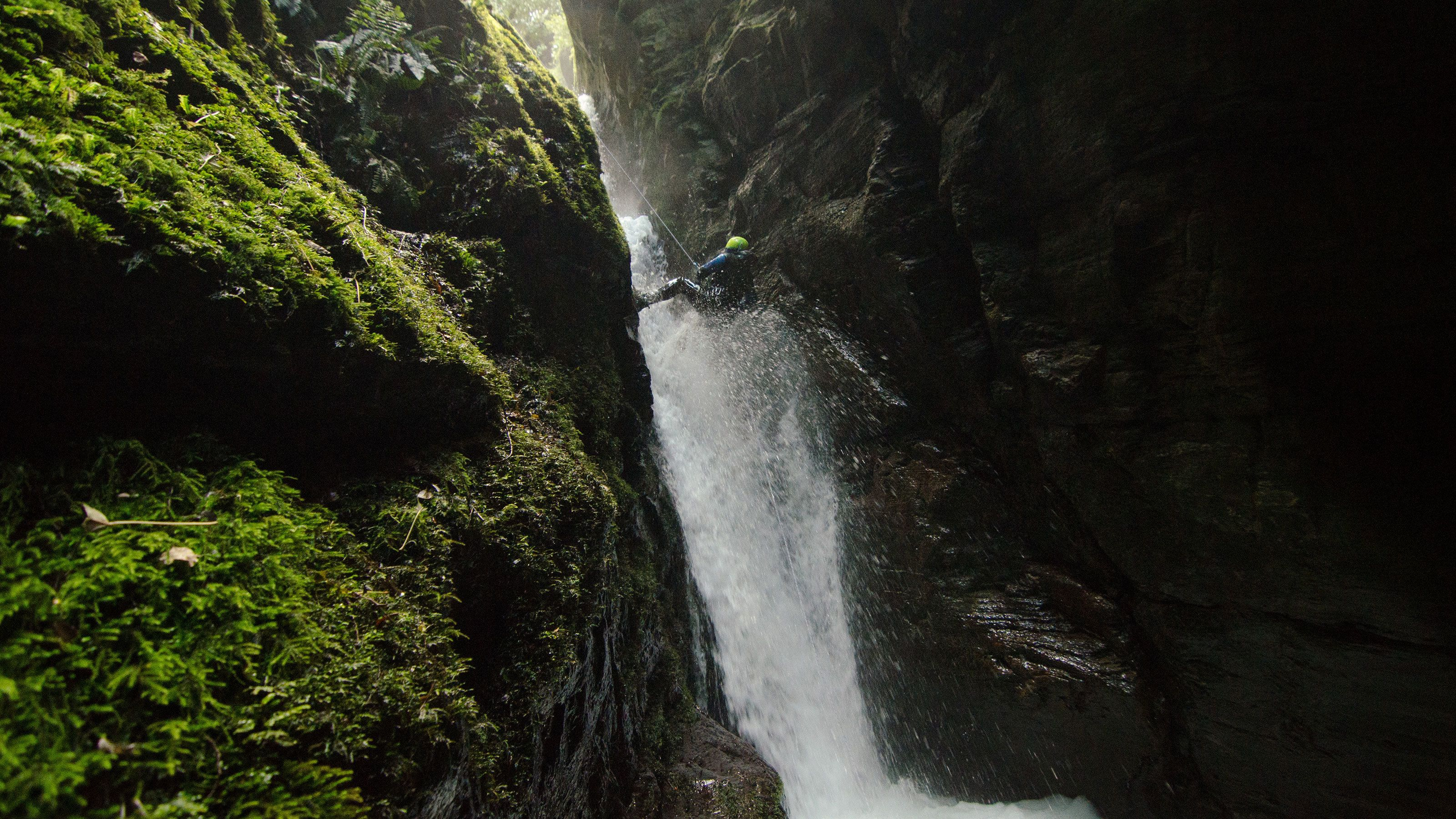Person rappelling down waterfall in New Zealand