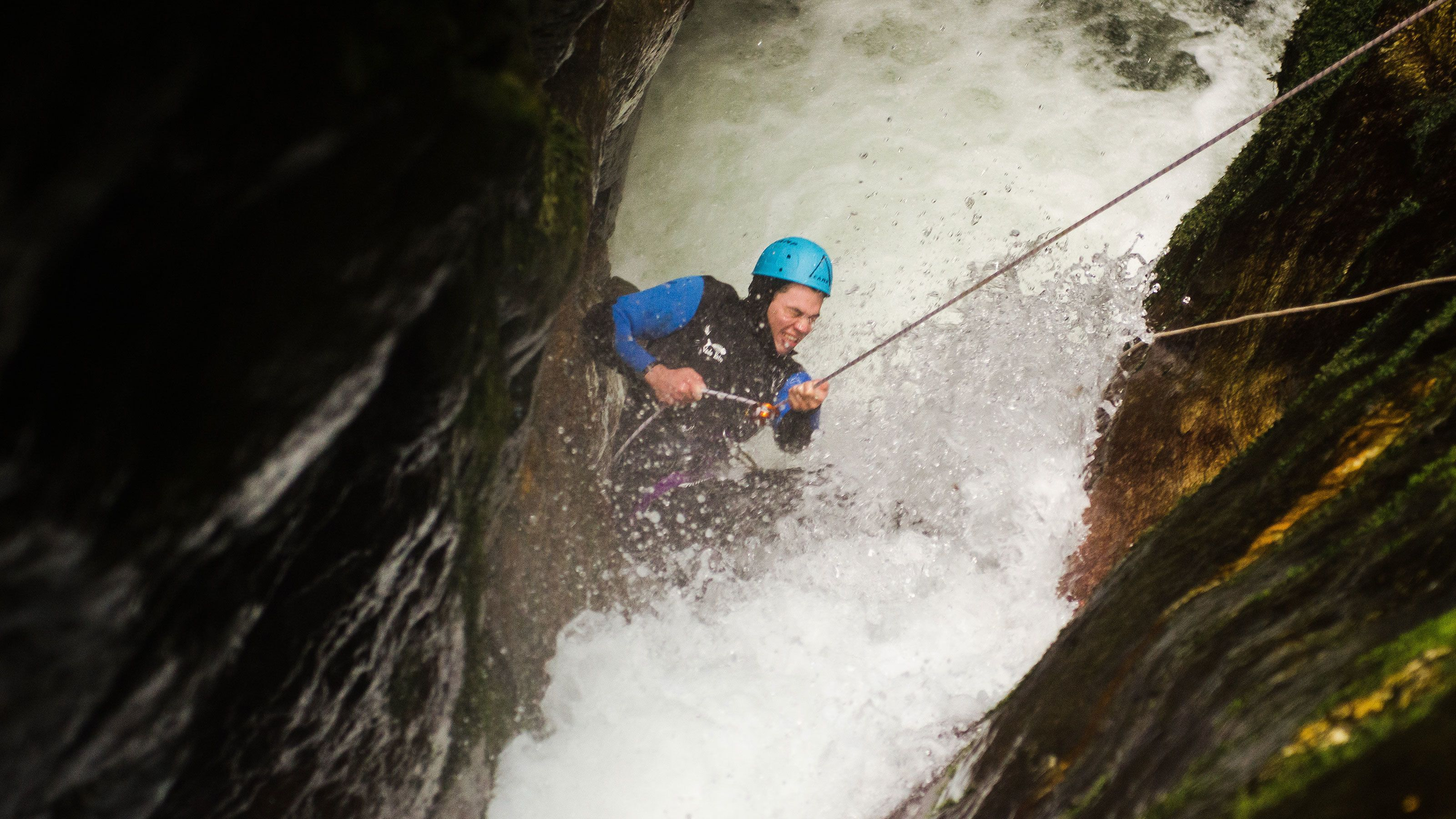 Man rappelling into waterfall in New Zealand
