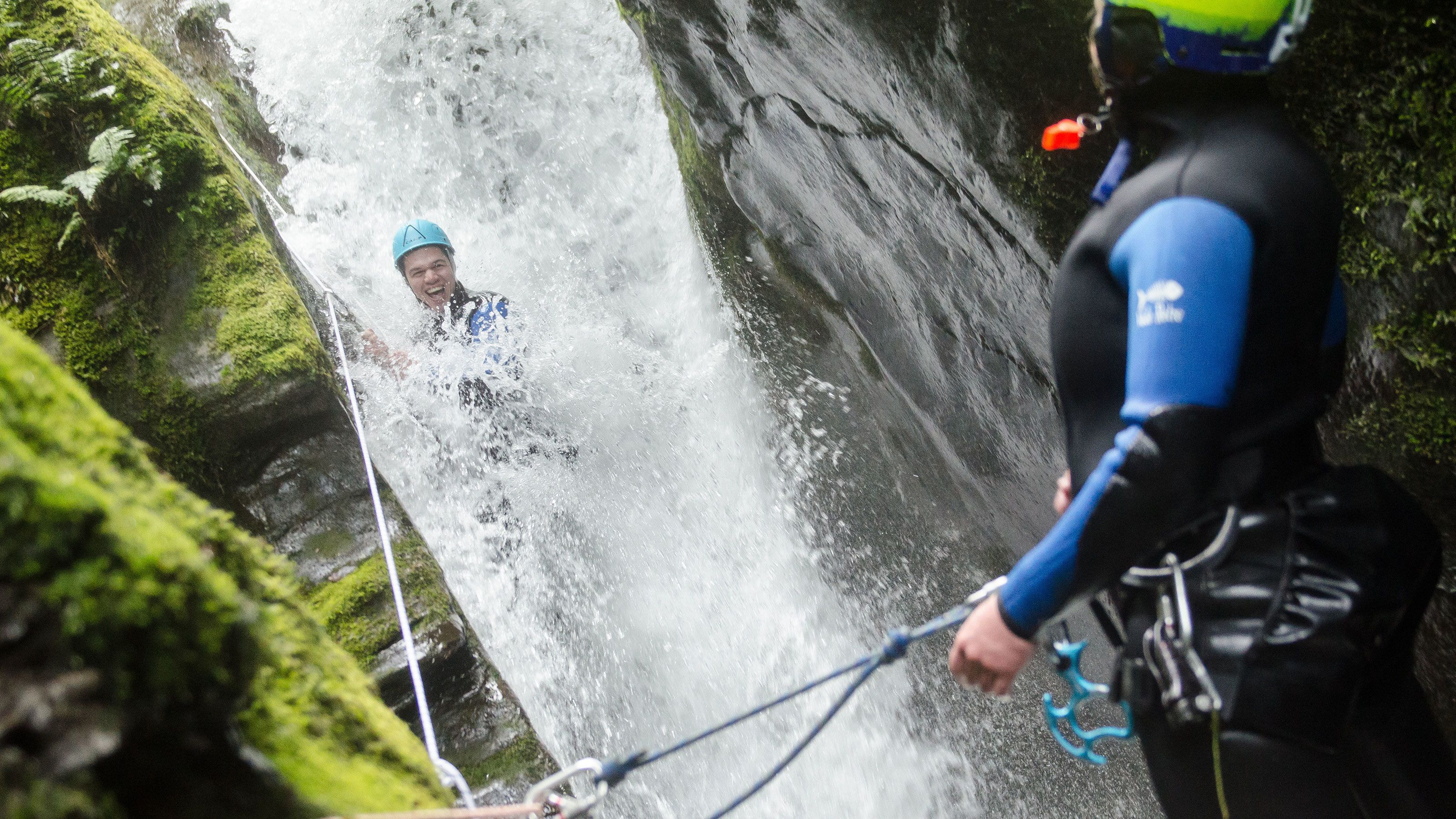 Person sliding down waterfall on New Zealand adventure