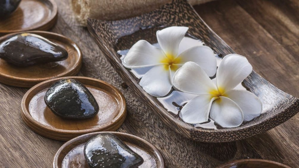 Close up of massage stones and flowers.