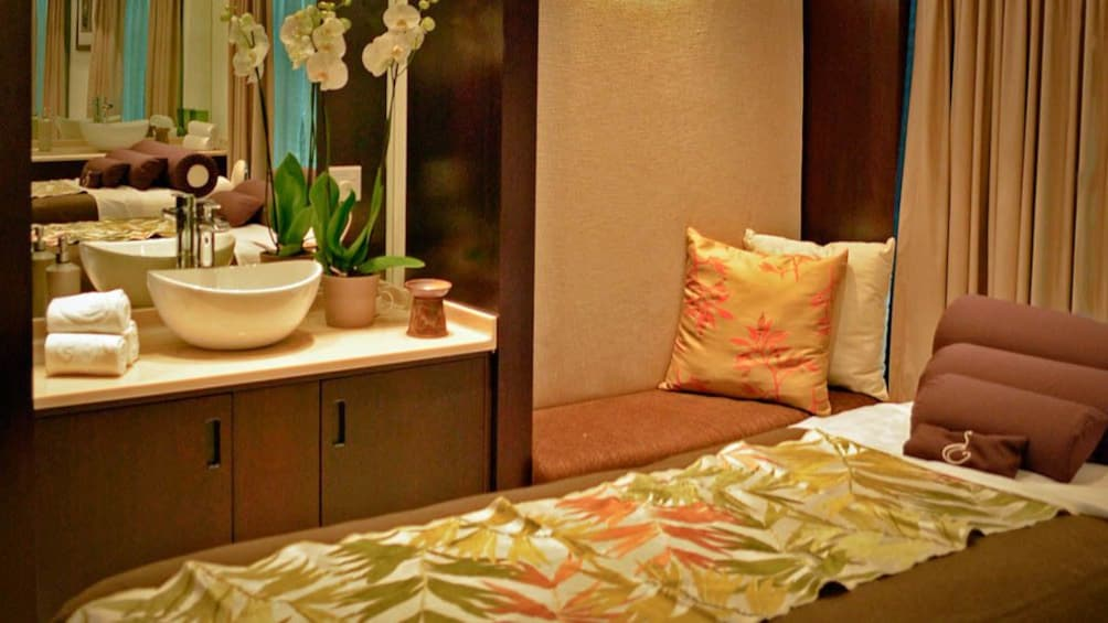 View of luxury massage room, with bed, and sink.