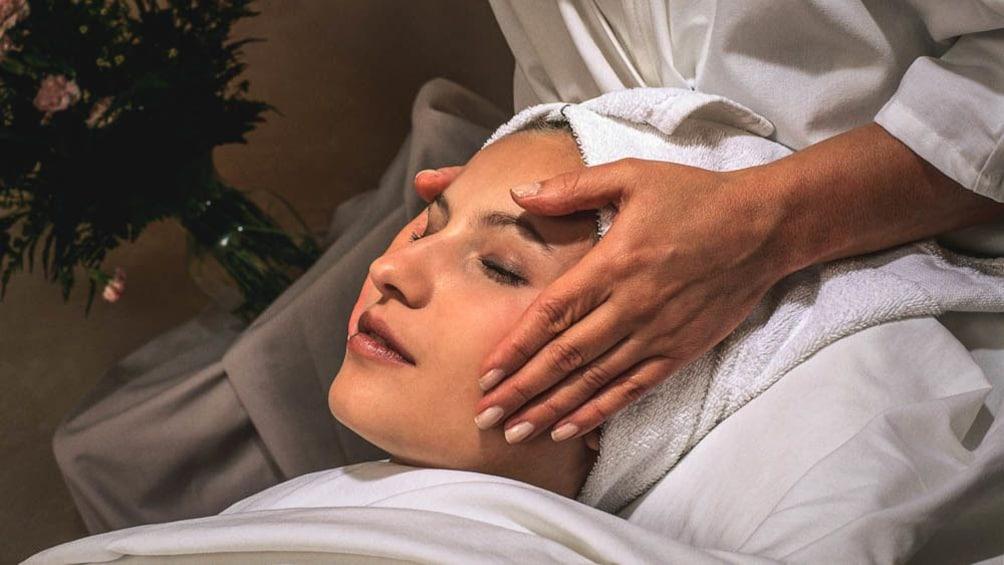 Close up of woman receiving facial massage.