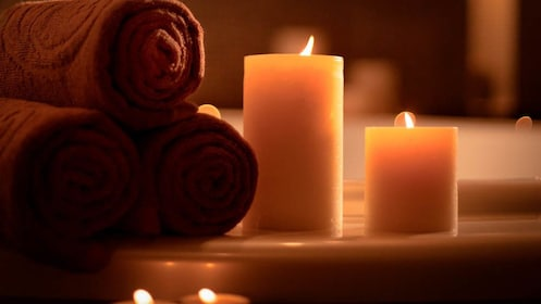 Close up of towels and lit candles by bathtub.
