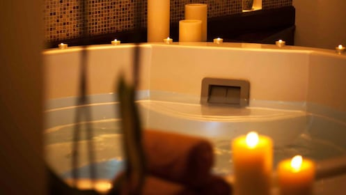 View of bathtub in treatment room surrounded by lit candles.