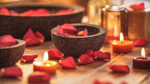 Close up of red rose pedals and lit candles.