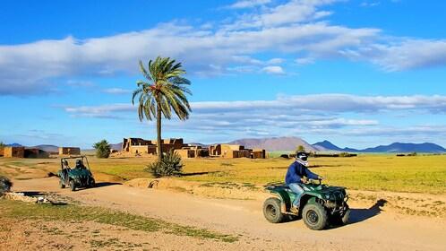 riding a quad bike through a dirt road in Morocco