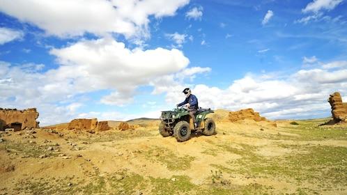 quad biker riding through the rocky desert terrain in Morocco