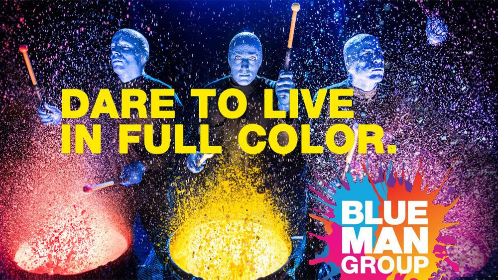 Blue Man Group banging on paint covered drums in New York