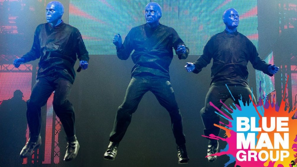 Show item 5 of 5. Blue Man Group jumping in the air onstage in New York