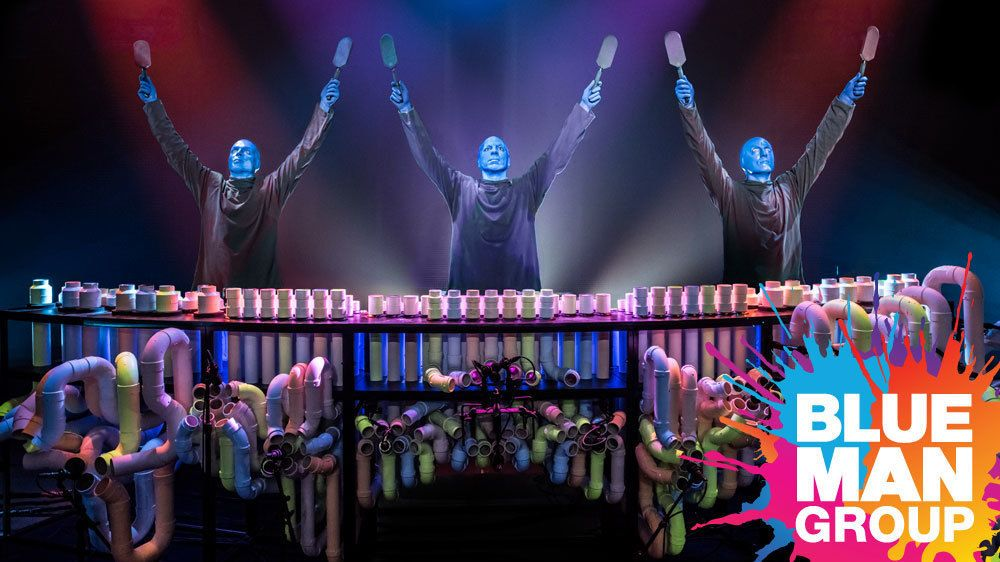 Blue Man group with rows of colored pipes onstage in New York
