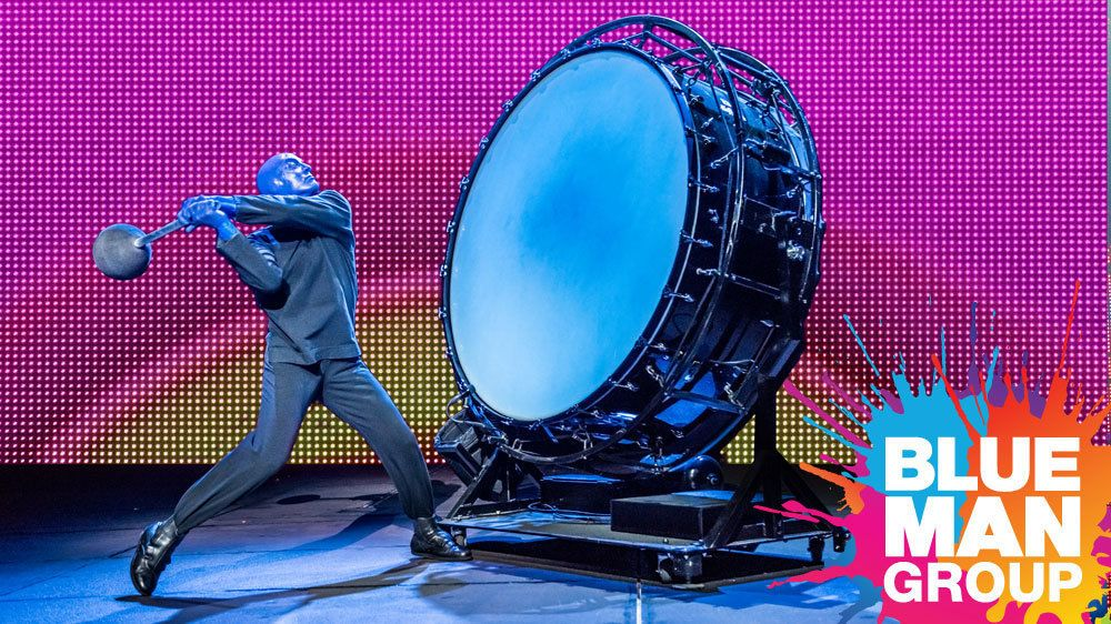 Blue Man banging on a large drum onstage in New York