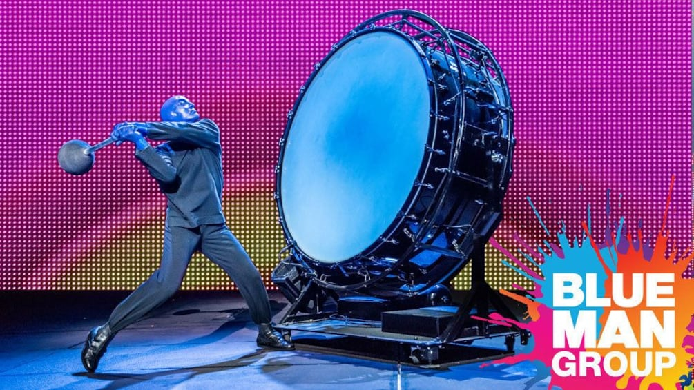 Show item 2 of 5. Blue Man banging on a large drum onstage in New York