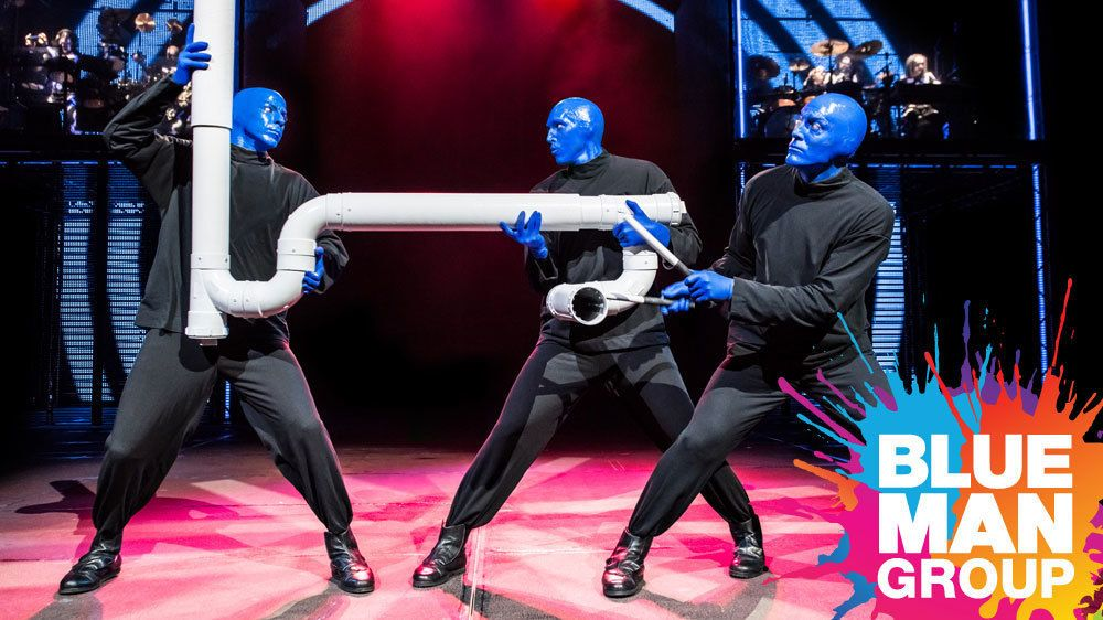 Blue Man Group playing a pipe during a performance in New York