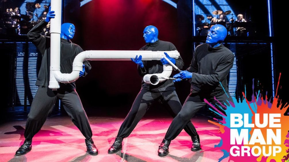 Show item 3 of 5. Blue Man Group playing a pipe during a performance in New York