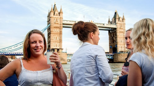 A group of ladies in front of the tower bridge in England