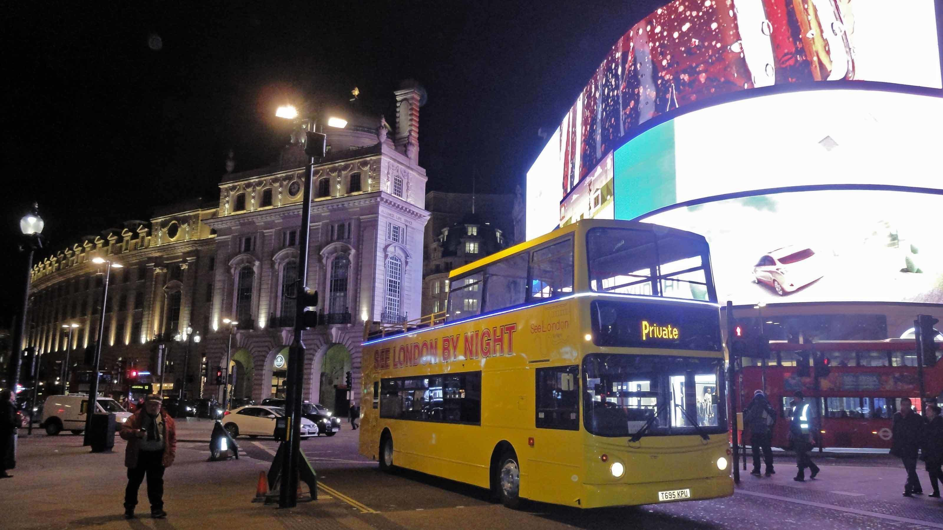 tour bus by big bright billboard in London
