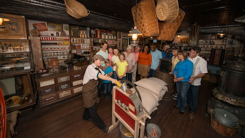 Oldest Store employee grinding corn for a tour group in St Augustine
