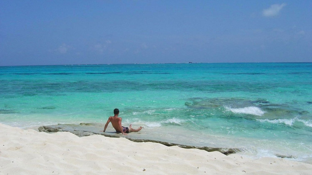 Show item 3 of 4. man sitting on the beach in San Andres