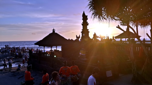 sun setting by the beach temple in Bali