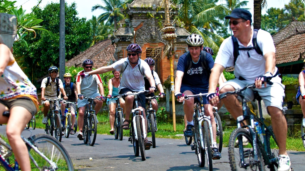 Show item 1 of 5. cyclists riding through a village in Bali
