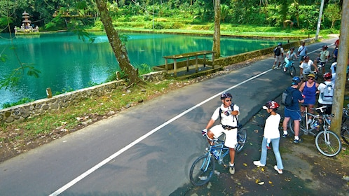 cyclists taking a break next to a village pond in Bali