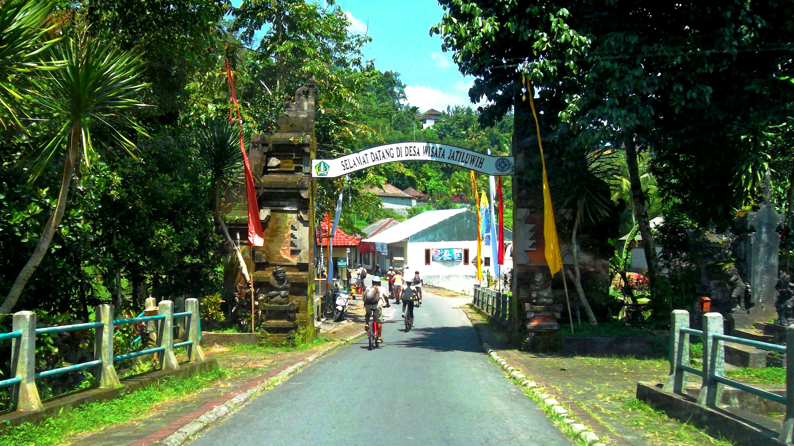 cyclists entering a small village in Bali