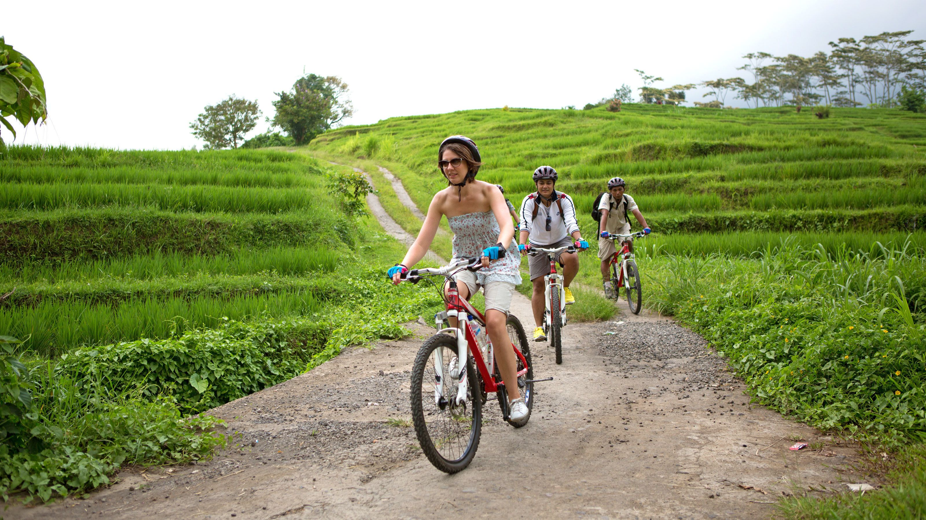 cyclists biking down a hilly dirt path in Bali