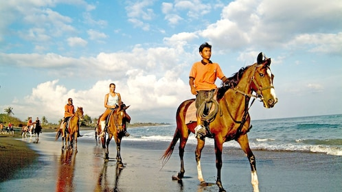 group riding horses along the beach in Bali