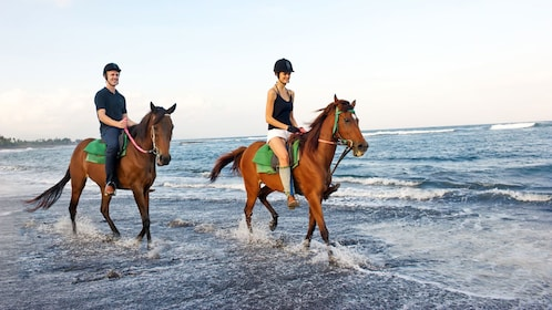 couple riding horses along a beach in Bali