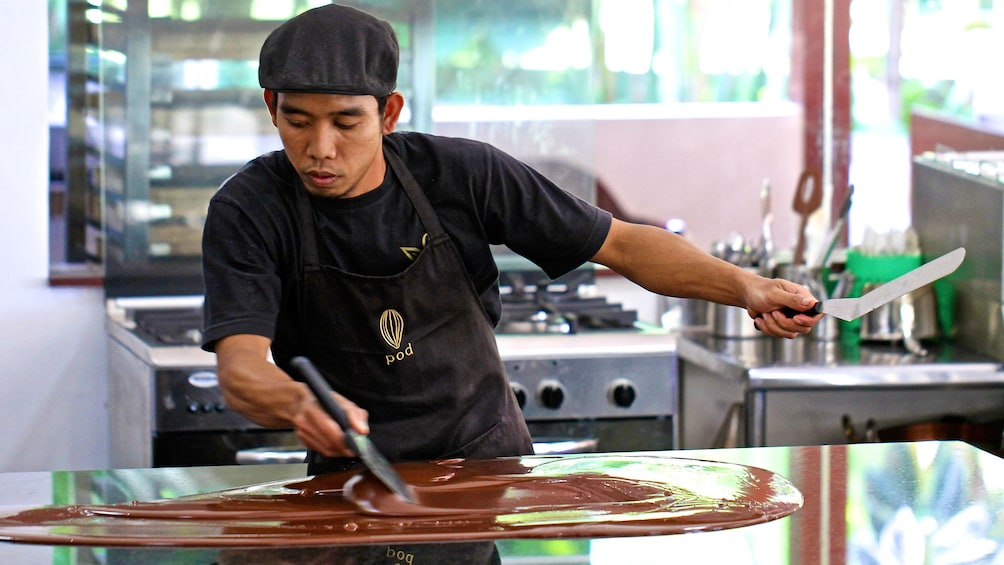 Tampilkan item 2 dari 5. employee thinning out melted chocolate on a countertop in Bali