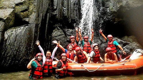 Group on raft and in water waving to camera