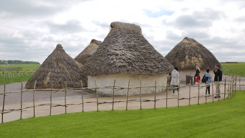 Group walking near thatched roof huts at Stonehenge in England