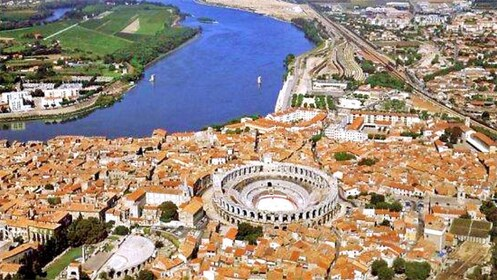 round colosseum amidst the red town roofs of Provence