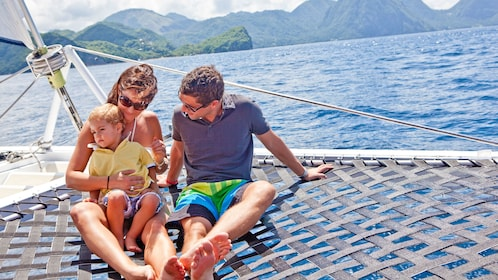 couple and toddler basking in the sun on a catamaran in Saint Lucia