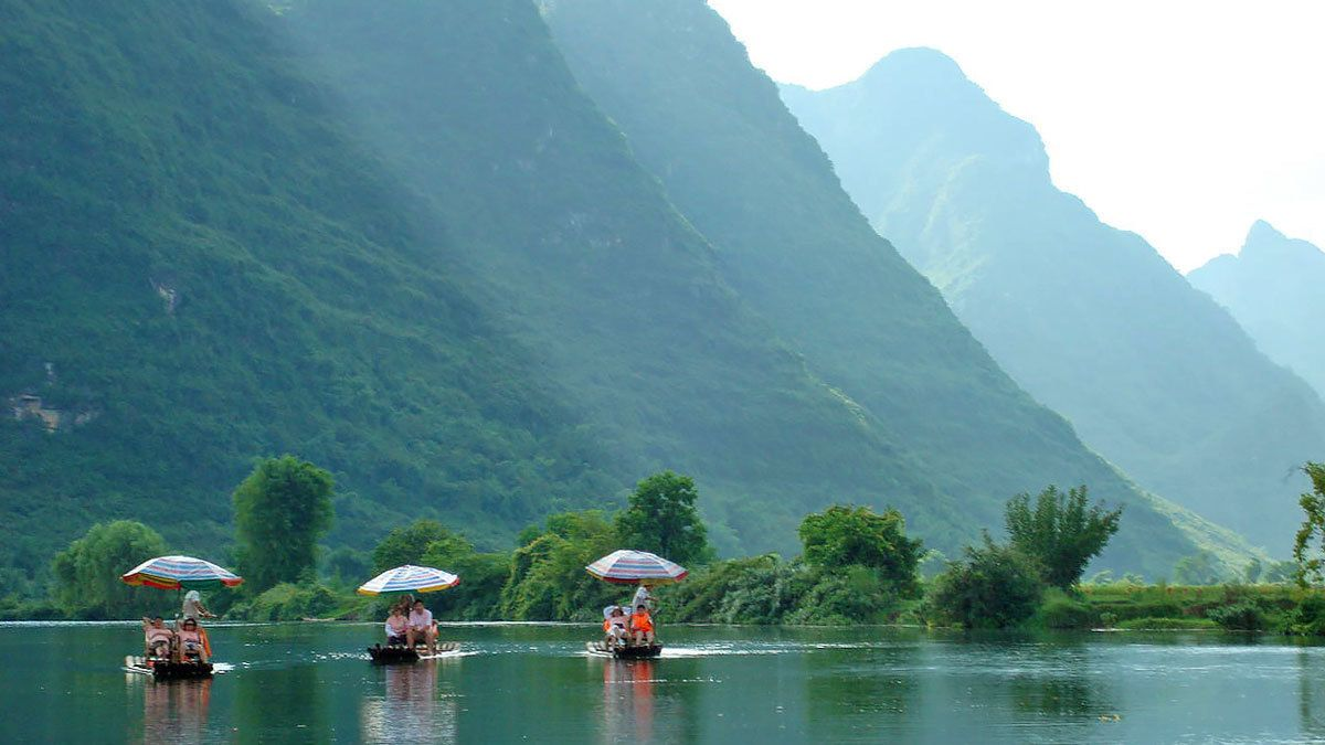 passengers riding on small paddled rafts in Guilin